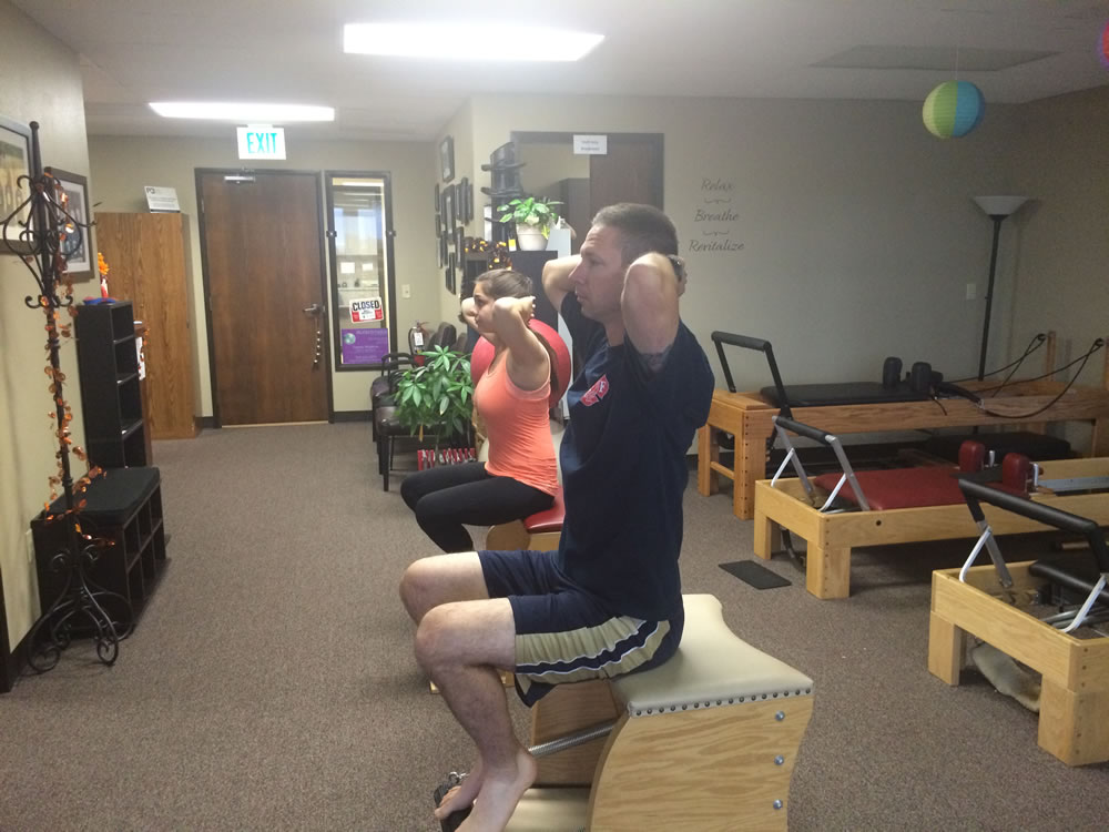 Two People Participating in a Chair Pilates Class