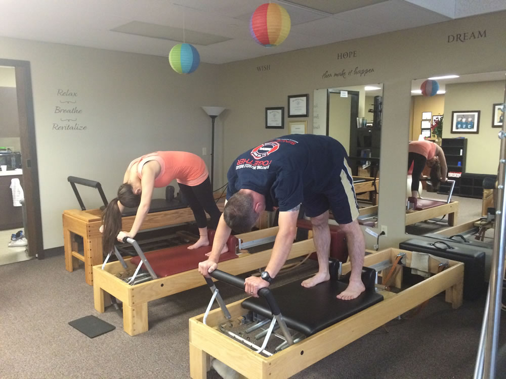 Two People Participating in a Reformer Pilates Class